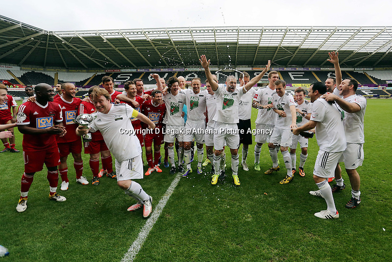 Pictured: Adam Woodyatt from Eastenders with the winning trophy flees to the left to avoid champagne sprayed by team mate Kevin Cooper (2nd R) after the end of the game. Sunday, 01 June 2014<br /> Re: Celebrities v Celebrities football game organised by Sellebrity Scoccer, in aid of Swansea City Community Trust, at the Liberty Stadium, south Wales.