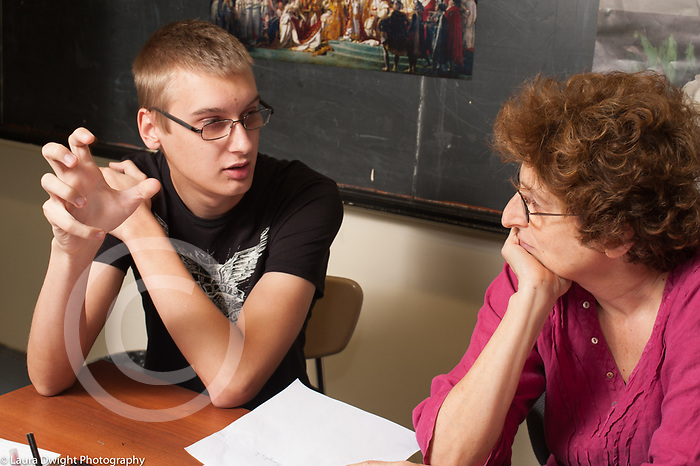 Education High School female teacher listening to male student talk in conference situation