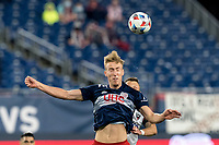 FOXBOROUGH, MA - APRIL 24: Adam Buksa #9 of New England Revolution heads the ball during a game between D.C. United and New England Revolution at Gillette Stadium on April 24, 2021 in Foxborough, Massachusetts.