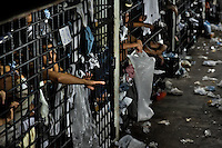 """Mara gang members are seen behind the bars of overcrowded cells at the detention center in San Salvador, El Salvador, 20 February 2014. Although the country's two major gangs reached a truce in 2012, the police holding cells currently house more than 3000 inmates, five times more than the official built capacity. Partly because the ordinary Mara gang members did not break with their criminal activities (extortion, street-level distribution of drugs, etc.), partly because Salvadorean police still applies controversial anti-gang law which allows to detain almost anyone for """"suspicion of gang membership"""". Accused young men are held in police detention centers where up to 25 inmates may share a cell of five-by-five metres. Here, in the dark overcrowded cages, under harsh and life-threatening conditions, suspected gang members wait long months, sometimes years, for trial or for to be transported to a regular prison."""
