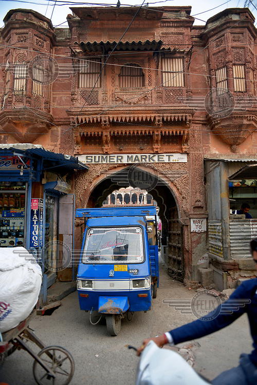 A trades vehicle leaves through the ornate main entrance to Sumer Market.