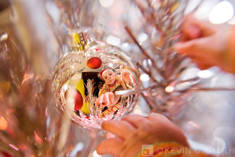 Close up of silver glass ball Christmas ornament with reflection of a 4 month old infant, caucasian, with Santa hat on, reaching for ornament, hands visible, ornament is hanging on a 60's retro aluminum christmas tree, selective focus.