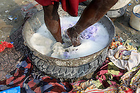 A man uses his feet to wash clothes in a metal bowl suspended by a vehicle tire.<br /> <br /> To license this image, please contact the National Geographic Creative Collection:<br /> <br /> Image ID: 1925812 <br />  <br /> Email: natgeocreative@ngs.org<br /> <br /> Telephone: 202 857 7537 / Toll Free 800 434 2244<br /> <br /> National Geographic Creative<br /> 1145 17th St NW, Washington DC 20036