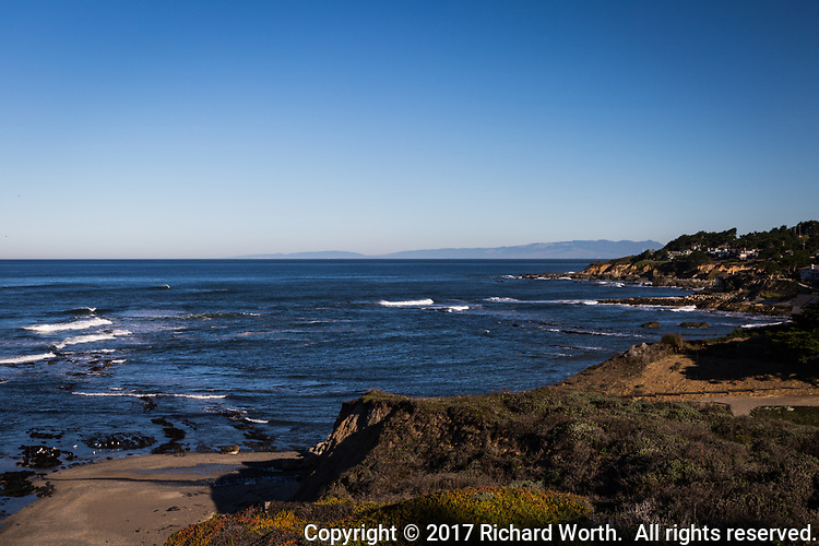 Coastal scene with gentle waves, rugged shoreline and clear blue sky with copy space.