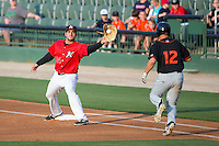 Kannapolis Intimidators first baseman Nick Basto (14) stretches for a throw as TJ Olesczuk (12) of the Delmarva Shorebirds runs down the line at CMC-Northeast Stadium on June 6, 2015 in Kannapolis, North Carolina.  The Shorebirds defeated the Intimidators 7-2.  (Brian Westerholt/Four Seam Images)