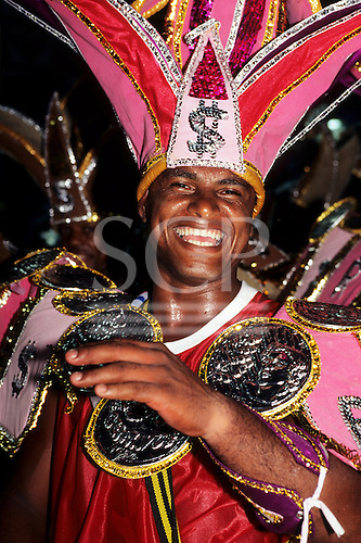 Rio de Janeiro, Brazil. Man wearing an  elaborate costume themed on money with a large headdress with dollar signs; Samba school, Carnival.