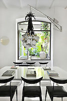 An unusual wall light with a cluster of globes suspended from a steel arm hangs above a white dining table and black dining chairs.