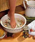 Wellness fuer die Fuesse - Frauenfuß taucht in eine Schuessel mit Kraeuterbad, Rosenblaettern und Thymian | woman's foot dipping into bowl with herbs, rose pedals and thyme
