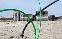 Nederland - Amsterdam - 2021.   Op het nieuw aangelegde Centrumeiland worden huizen gebouwd naar eigen ontwerp. Het wordt een van de duurzaamste ontwikkellocaties van de stad, mede door het systeem van warmte koude opslag WKO. Daarmee worden de huizen op het hele eiland voorzien van warmte en koude uit de bodem. Bouwgrond met kabels.  Foto ANP / Hollandse Hoogte / Berlinda van Dam