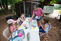 Ruth Teague hands out information about caterpillars during Butterfly Day Camp Tuesday Aug. 3, 2021 at the Botanical Garden of the Ozarks in Fayetteville. Areas of study include habitat, life cycles, coloration and defense and butterfly behaviors. The camp goes until Aug. 6th. For more information about activities at the garden see https://www.bgozarks.org/. Visit nwaonline.com/21000804Daily/ and nwadg.com/photo. (NWA Democrat-Gazette/J.T. Wampler)