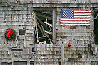 Christmas ornament and American flag on the the side of an abandoned house.