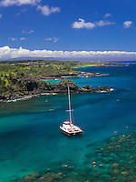 Snorkelers and tour boat Hula Girl in Honolua Bay, with Kapalua in distance, western Maui.