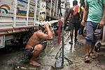 A man bathes under a street tap at burrabazzar in Kolkata.  Whole sale market reopened in Kolkata few days back midst 21 days lock down in India due to covid 19 pandemic. Kolkata, West Bengal, India. Arindam Mukherjee.