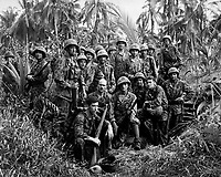 These men have earned the bloody reputation of being skillful jungle fighters.  They are U.S. Marine Raiders gathered in front of a Jap dugout on Cape Totkina on Bougainville, Soloman Islands, which they helped to take.  January 1944. (Navy)<br /> Exact Date Shot Unknown<br /> NARA FILE #: 080-G-205686<br /> WAR & CONFLICT BOOK #:  1200