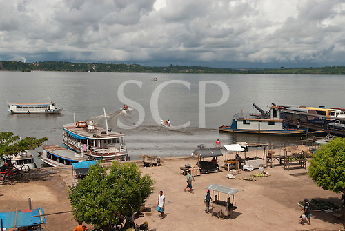 Itaituba, Amazon, Tapajos river, Para State, Brazil. Quay at the port with riverboats, street vendors and a ferry boat ready to depart.