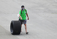 Jul 19, 2020; Clermont, Indiana, USA; An NHRA fan wearing a mask rolls a tire through the pits during the Summernationals at Lucas Oil Raceway. Mandatory Credit: Mark J. Rebilas-USA TODAY Sports