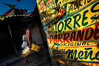 An Afro-Colombian water carrier walks around the wall, covered with Champeta music propaganda, in the market of Bazurto in Cartagena, Colombia, 5 December 2018. Far from the touristy places in the walled city, a colorful, vibrant labyrinth of Cartagena's biggest open-air market sprawls to the Caribbean seashore. Here, in the dark and narrow alleys, full of scrappy stalls selling fruit, vegetables and herbs, meat and raw fish, with smelly garbage on the floor and loud reggaeton music in the air, the African roots of Colombia are manifested.