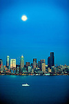 Moon rises over downtown Seattle as tour boat operated by Argosy Tours cruises Elliott Bay.