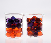 ENTROPY: ILLUSTRATION<br /> (Variations Available)<br /> Arrangement of Beads in 2 Beakers<br /> Two beakers contain orange & purple beads.  Because entropy can be viewed as a measure of disorder, the arrangement in which the colors are separated represents a system of lower entropy than the one in which the colors are mixed.