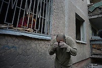 A man wipes his eyes off from dust near his house damaged by shelling.