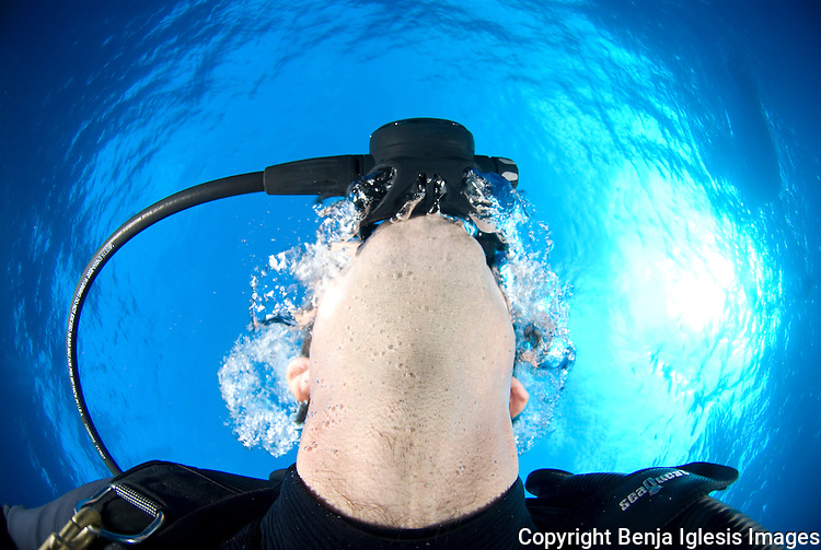 Underwater photo pf a diver exhaling from regulator Maui Hawaii.