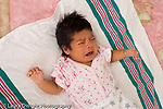 newborn baby girl one month old  Mexican American on back closeup crying horizontal