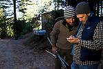 Mountain Lion (Puma concolor) biologists, Max Allen and Paul Houghtaling, checking satellite tracking data on phone near house, Santa Cruz Puma Project, Santa Cruz, Monterey Bay, California
