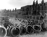 A pile of 85,000 solid tires for A.E.F. motor vehicles is one of the treasures of Langres, France.  Shows men of Motor Transport Corps, assisted by German prisoners, building up wall of rubber to greater height.  January 6, 1919.  (Army)<br /> NARA FILE #:  111-SC-44921<br /> WAR & CONFLICT BOOK #:  588