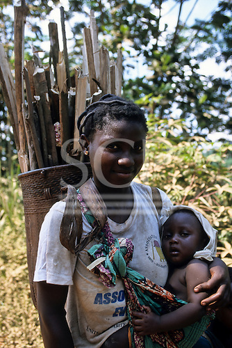 La Gongue, Gabon. Young Gabonese women with her baby in a sling carrying a pannier basket full of firewood.