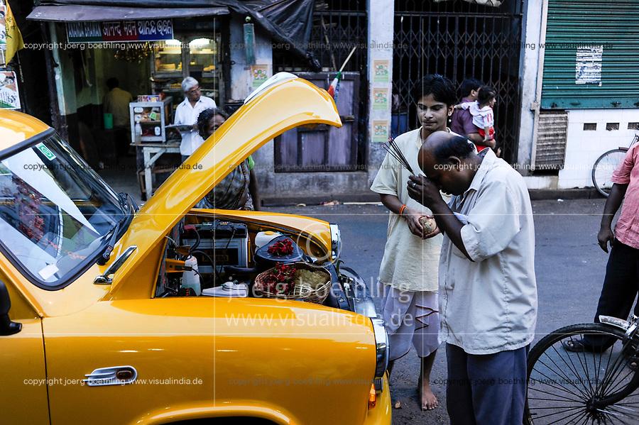 INDIA Kolkata Calcutta , owner and taxi driver prays to Hindu gods for blessings for his new HM Ambassador yellow cab at Kali Ghat  / INDIEN Kolkata Kalkutta , Jay Dev Chowdhury Taxifahrer und Autobesitzer spricht ein Gebet nach Weihung seines neuen Autos durch einen Brahmanen Priester am Kali Ghat, der HM Ambassador laeuft heute noch neu nach Vorlage des Oxford Morris bei HM Hindustan Motors fabrikneu vom Band
