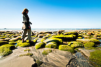 A woman walking on Carters Beach in Westport - Buller Region, Central West Coast, New Zealand