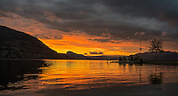Fine Art Landscape Photograph of the sun setting on lake Okanagan in Penticton BC Canada. The lighting over Okanagan lake was spectacular, and the silhouetted statues remind everyone of Penticton. The beautiful lakes and mountains makes this a place of memories.