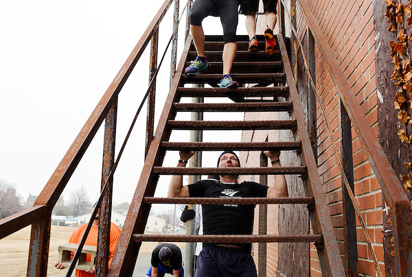 December 22, 2014. Lexington, North Carolina.<br />  Mayor Newell Clark performs pull-ups on the steps of the abandoned Lexington Furniture factory as other members of his workout group run the stairs.<br />   Newell Clark, the 43 year old mayor of Lexington, NC, leads a group of friends and colleagues on a 4 times a week exercise routine around downtown. The group uses existing infrastructure, such as an abandoned furniture factory, loading docks, stairs, and handrails to get fit and increase awareness of healthy lifestyles in a town more known for BBQ.<br /> Jeremy M. Lange for the Wall Street Journal<br /> Workout_Clark