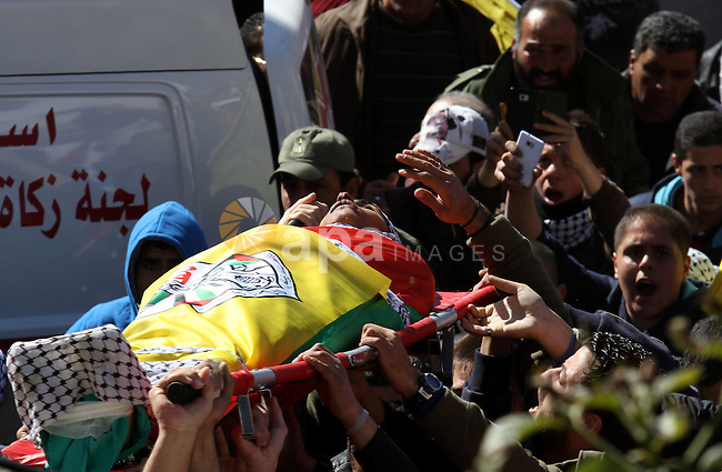 """Mourners carry the body of Palestinian Ahmad Najjar, 20, who was shot dead by Israeli soldiers, during his funeral in the West Bank village of Burin near Nablus February 1, 2015. Israeli soldiers shot dead Najjar on Saturday in the occupied West Bank, the military and a Palestinian security official said. An Israeli military spokeswoman said soldiers saw two Palestinians throwing a fire bomb towards a road near the Palestinian city of Nablus and """"identifying an immediate threat shot toward the suspects' lower extremities"""". A Palestinian security source said one of the Palestinians shot by the soldiers was killed, but gave no further details. The Israeli military said it was searching for the second man. Photo by Nedal Eshtayah"""