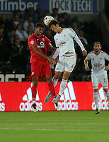 Pictured: Ki Sung Yueng of Swansea (R) heads the ball over a York player Tuesday 25 August 2015<br /> Re: Capital One Cup, Round Two, Swansea City v York City at the Liberty Stadium, Swansea, UK.