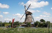 Molen bij Kinderdijk. Een historische  zalmschouw vaart langs de molen