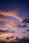St. Lucia. View out to sea at sunset with golden, yellow and orange sky and clouds.