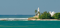Galle Lighthouse, old mosque and distant ship in the turquoise seas of southern Sri Lanka.