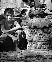 Ein kleiner Junge neben einer Mayaskulptur eines Schädels in Copan, Honduras 1970er Jahre. A boy beside a Mayan sculpture of a skull at Copan, Honduras 1970s.