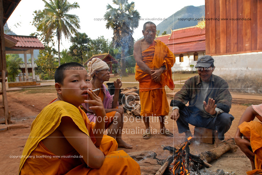 LAOS Nam Ou, village Muang Ngoi, buddhist monks in monastery, monks sitting at fire and smoke cigarette / LAOS, Nam Ou, Dorf Muang Ngoi, buddhistische Moenche in einem Kloster, Moenche sitzen am Lagerfeuer un rauchen Zigaretten