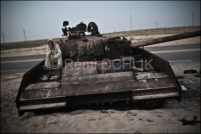 © Remi OCHLIK/IP3 -  Benghazi March 25, 2011 - A rebel fighter rest on a destryed tank hit by French war jets.