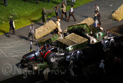 "27 JUL 2012 - LONDON, GBR - Performers dressed as 19th Century farmworkers load the rural scenery and props from the ""Green and Pleasant Land"" section onto a tractor and trailer at the start of the ""Pandemonium"" section of the Opening Ceremony of the London 2012 Olympic Games in the Olympic Stadium in the Olympic Park, Stratford, London, Great Britain (PHOTO (C) 2012 NIGEL FARROW)"