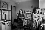Shetland Islands, crofting family, mother and daughter in kitchen. the mother is knitting a Fair Isle jumper, one has been washed and is hung up to dry before being sold through a local shop. 1979.