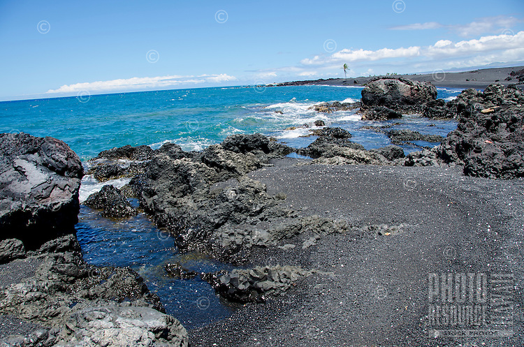 The rocky shoreline of Keawaiki Bay, with a lone palm tree in the distance, Hawai'i Island; an 1859 Mauna Loa eruption overflowed into this area, which was also the site of an ancient Hawaiian settlement and heiau (or temple).