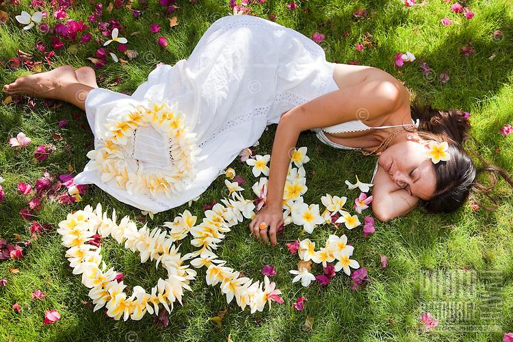Beautiful Hawaiian woman lying down next to the fragrant plumeria lei she made