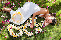 Beautiful Hawaiian woman lying down next to the fragrant plumeria lei she made