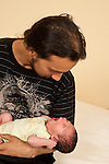 Newborn baby boy one week old held by young father
