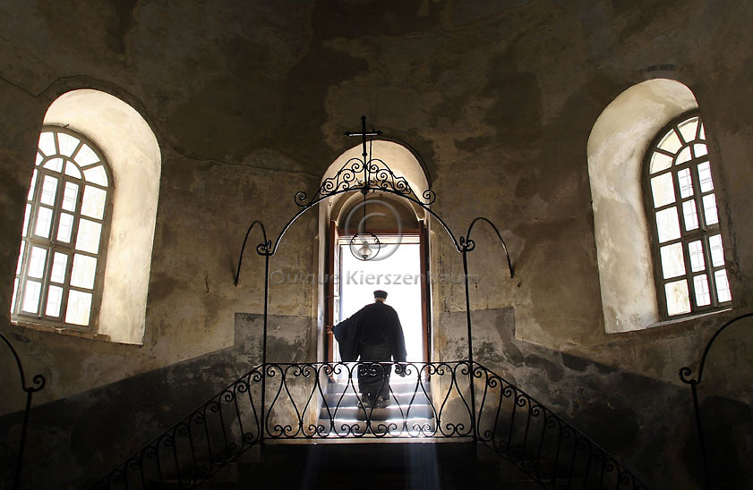 A Greek Orthodox priest is highlighted by a ray of light as they walk through the Church of the Nativity, the traditional site of Jesus birth on December 14, 2005. . Despite the wall and the restrictions Bethlehem is starting to prepare for the Christmas season, when many Christian converge on the town to worship in the birth place of Jesus Christ. Photo by Quique Kierszenbaum