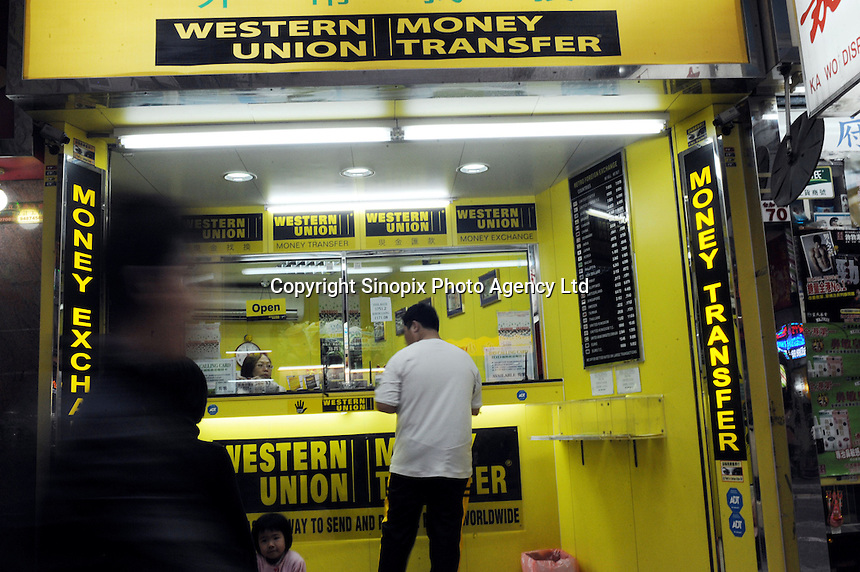 """People walk pass a currency exchange shop called """"Western Union"""" in Hong Kong. With a great number of money exchange shops, Hong Kong has made it very easy for consumers from all over the world to shop freely in this tax-free shopping paradise. ."""