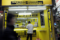 "People walk pass a currency exchange shop called ""Western Union"" in Hong Kong. With a great number of money exchange shops, Hong Kong has made it very easy for consumers from all over the world to shop freely in this tax-free shopping paradise. ."